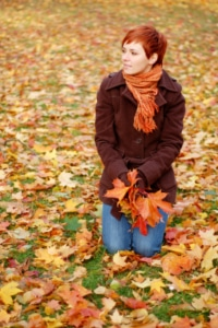 Woman Sitting in Fall Leaves